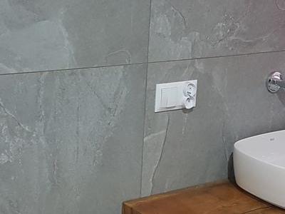 łazienka w dużych szarych płytach wykańczanie wnętrz